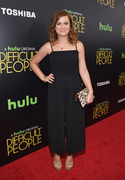 Amy Poehler styled her jumpsuit with a leopard-print clutch.