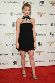 Lili Reinhart complemented her frock with embellished black cross-strap heels, also by Miu Miu.