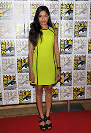Freida Pinto punctuated the bright yellow shift dress she wore to Comic-Con with a pair of standout black satin Alana sandals. The heels matched the black piping of her Michael Kors dress.