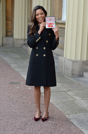 Naomie Harris visited the Queen to pick up her OBE medal wearing a classic black wool coat with gold buttons.