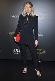 Fergie accessorized with a red Givenchy leather clutch for a bright pop to her black outfit.