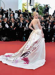 Elle Fanning looked downright darling at the Cannes Film Festival opening gala in a Vivienne Westwood Couture strapless gown that featured a flowing train with a whimsical print.