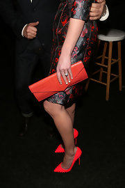 Katherine Heigl's bright pink clutch complemented her studded heels and floral dress at the J. Mendel runway show.