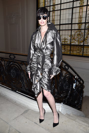 Paz Vega made an ultra-chic arrival at the Jean Paul Gaultier Haute Couture show wearing a ruffled silver trenchcoat from the label.