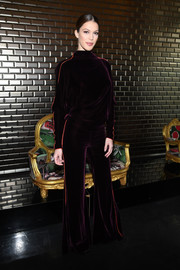 Iris Mittenaere donned a purple velvet jumpsuit with an open back and orange piping for the Jean Paul Gaultier Couture show.