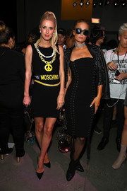 Paris Hilton layered a studded leather jacket over a lace-up LBD for the Jeremy Scott fashion show.