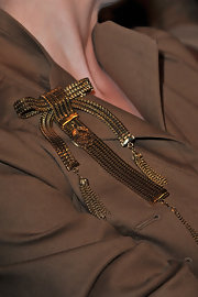 Dita accented her tan trench coat with a gold bow brooch.