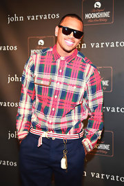 Chris Brown flashed his signature grin while wearing a pair of dark tint wayfarers.