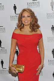 Raquel Welch partnered her red dress with a gold flap clutch at the John Wayne Cancer Institute event.