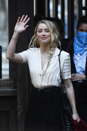 Amber Heard paired a pleated cream blouse with a black skirt for Johnny Depp's libel trial.
