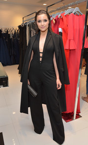 Olivia Culpo looked effortlessly sophisticated in a black tux-style jumpsuit by Jovani, featuring a strappy, down-to-the-navel neckline, during the label's LA flagship opening.