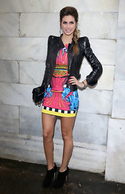 Melissa Satta paired a funky print dress with a pointed shoulder leather jacket at the Just Cavalli runway show in Milan.