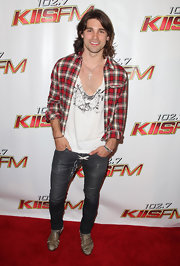 Justin layered a red plaid button-down over a v-neck graphic tee, exposing a bit of chest hair.