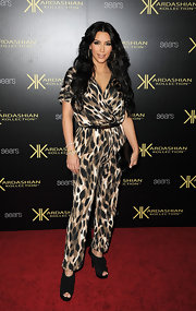 Kim Kardashian gets wild at the Kardashian Kollection launch in a leopard print jumpsuit from the line.