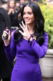 Katy Perry waves to her fans while promoting her fragrance, Purry. She paired her deep purple dress with matching bracelets.