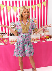 Kelly looked spring-chic in a colorful, printed dress with metallic embellishments and a tied waistline.