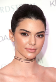 Kendall Jenner kept her makeup look natural with a bronzed eyeshadow and long lashes at the Kendall + Kylie collection launch.