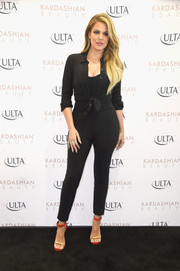 Khloe Kardashian styled her jumpsuit with a black Theory button-down tied at the waist.