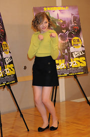 Chloe is ready to fight in a yellow sweater and buttoned wool skirt.