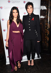 Kim Kardashian stuck to her usual style in a plunging plum gown at an event for the Elizabeth Taylor AIDS Foundation.