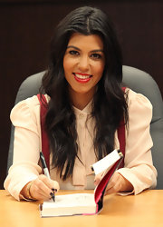 Kourtney Kardashian wore a sexy, shiny red lipstick at a signing of her new book, 'Dollhouse.'