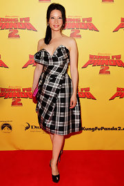 Lucy Liu added feminine flair to her plaid cocktail dress at the Australian premiere of 'Kung Fu Panda 2' with a fuchsia satin Party Time clutch.