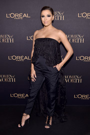 Eva Longoria went frilly in a strapless black Noon by Noor jumpsuit, featuring a layered bodice that cascaded into a long train, at the L'Oreal Paris Women of Worth celebration.