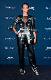 Amber Valletta looked very daring (from the waist up at least) at the LACMA Art + Film Gala in a blue Gucci jumpsuit featuring a mesh and feather bodice.