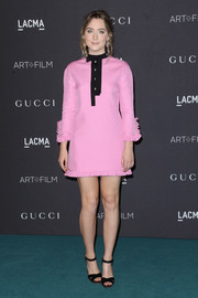 Saoirse Ronan teamed her dress with simple black cross-strap sandals, also by Gucci.
