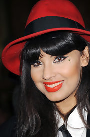 Jameela Jamil chose bright brick-red lips at the PPQ Spring/Summer 2013 show during London Fashion Week.