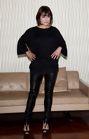Valentina paired her black leather pants with peep toe pumps. The heels feature bold t-straps.