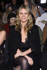 Gwyneth Paltrow sat front row at the La Perla fashion show wearing a black wool coat over a lace dress.