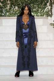 Naomi Campbell was equal parts sultry and elegant in an embroidered blue coat layered over a lingerie-inspired dress at the La Perla fashion show.