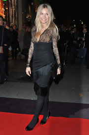 Sienna Miller wore a black lacy cocktail dress with a fringed skirt to attend the 135 Years of French Legerete in Paris.