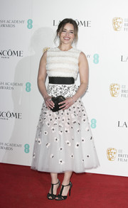 Emilia Clarke rounded out her look with a black hard-case clutch by Roger Vivier.