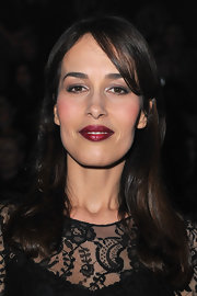 Dolores Chaplin attended the Lanvin fall 2012 fashion show wearing a vivid metallic cranberry-colored lipstick.
