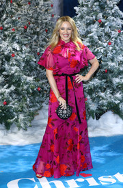 Kylie Minogue attended the UK premiere of 'Last Christmas' wearing a fuchsia maxi dress with red floral embroidery.