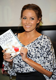 Lauren Conrad has left a few strands loose from her two french braids pulled back into a bun to soften the look.