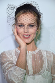 Eva Herzigova attended the 'Le Bal Surrealiste' Dior show wearing an updo adorned with a black birdcage veil.