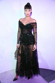 Bella Hadid flashed plenty of skin in a sheer black off-the-shoulder gown by Dior during the label's 'Le Bal Surrealiste' show.