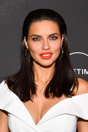 Adriana Lima lit up her face with some red-orange lipstick.