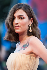 Eleonora Carisi complemented her 'do with a pair of scalloped chandelier earrings.