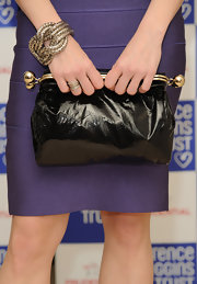 Neve Campbell arrived at the Lighthouse Gala Auction with a stylish oversized black clutch.