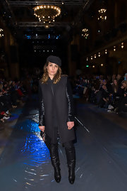 Noomi Rapace went for an androgynous-chic look with a black wool coat and knee-high boots during Mercedes-Benz Stockholm Fashion Week.