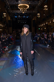 Noomi Rapace kept warm in edgy style with a pair of black knee-high boots and a silk-sleeved coat at the Local Firm fashion show.