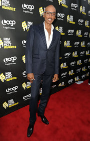 RuPaul showed off his dapper style in a navy blue pin stripped suit.