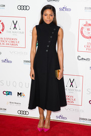 Naomie Harris rounded out her ensemble with a gold box clutch by Lee Savage.