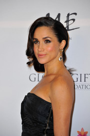 Meghan Markle amped up the glamour with a pair of crystal drop earrings teamed with side-swept curls at the London Global Gift Gala.