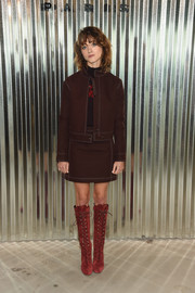 Natalia Dyer sealed off her look with a pair of knee-high lace-up boots.
