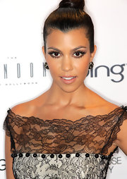Kourtney paired her sleek bun with cluster gemstone earrings.